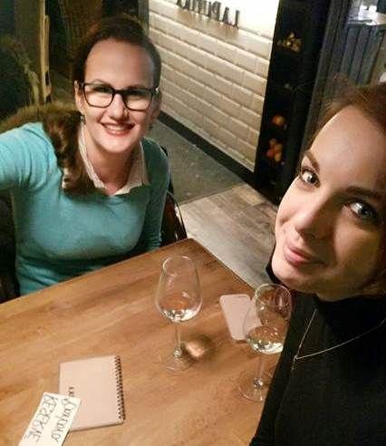 Dve kamarátky sa rozprávajú pri pohári vína